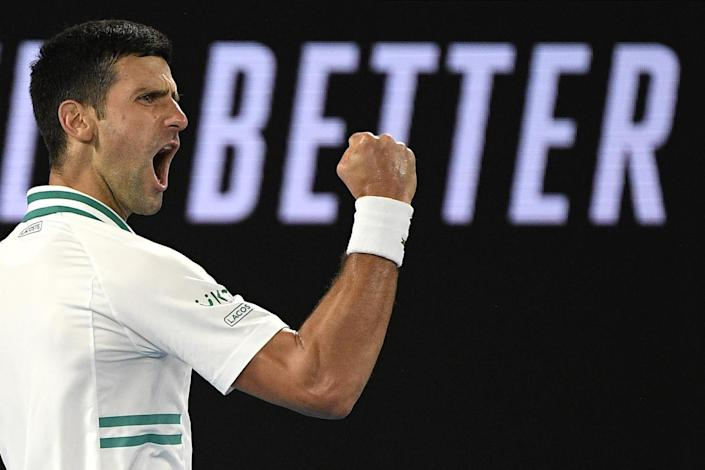 Novak Djokovic clenches a fist and yells in celebration.