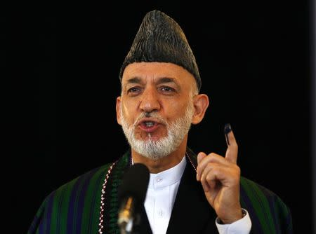 Afghan President Hamid Karzai holds up his ink-stained finger after voting in the presidential election in Kabul