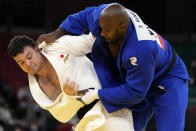 Aaron Wolf of Japan, left, and Teddy Riner of France compete during their gold medal match in team judo competition at the 2020 Summer Olympics, Saturday, July 31, 2021, in Tokyo, Japan. (AP Photo/Vincent Thian)