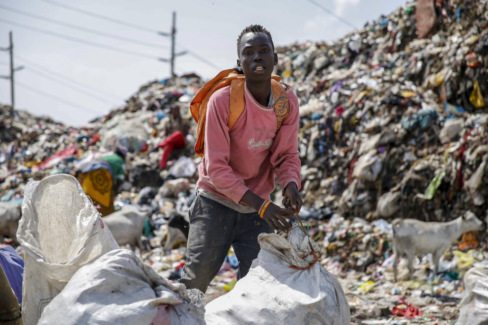 Mohamed Nassur, 17, scavenges for scrap metal to sell at Kenya's largest landfill Dandora where he now works after his mother lost her job and his school was closed due to the coronavirus pandemic, in Nairobi, Kenya Saturday, Sept. 26, 2020. The United Nations says the COVID-19 pandemic risks significantly reducing gains made in the fight against child labor, putting millions of children at risk of being forced into exploitative and hazardous jobs, and school closures could exacerbate the problem. (AP Photo/Brian Inganga)