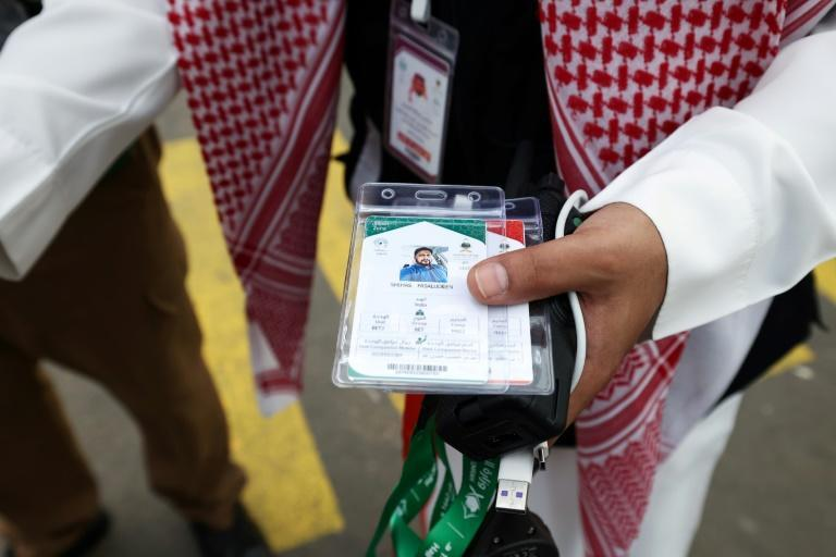 A Saudi member of staff checks pilgrims' hajj cards, allowing contactless access to religious sites, accommodation and transport, at a reception centre in Mecca
