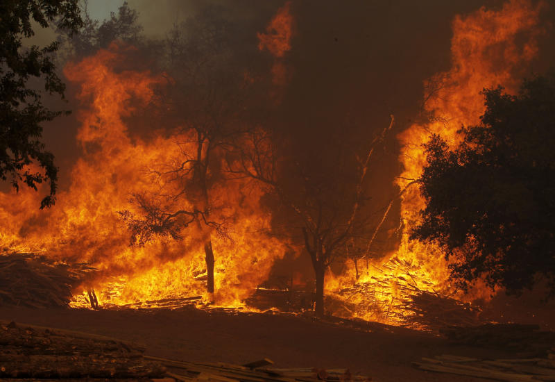 A large wildfire on Highway 71 near Smithville, Texas, Monday, Sep. 5, 2011 burns piles of lumber and ranch posts.  A roaring wildfire raced unchecked Monday through rain-starved farm and ranchland in Texas, destroying nearly 500 homes during a rapid advance fanned in part by howling winds from the remnants of Tropical Storm Lee.  (AP Photo/Erich Schlegel)