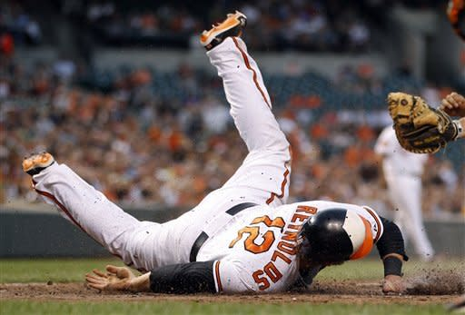 Baltimore Orioles' Mark Reynolds slides into home plate past Pittsburgh Pirates catcher Michael McKenry for a run on a sacrifice fly by Wilson Betemit in the fourth inning of a baseball game in Baltimore, Wednesday, June 13, 2012. (AP Photo/Patrick Semansky)