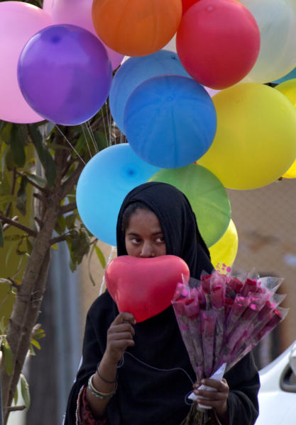 """A Pakistani girl waits to sell Valentine's balloons and roses to customers in Islamabad, Pakistan on Wednesday, Feb. 13, 2013. Supporters of Pakistan's main religious party Jamaat-e-Islami staged a protest against Valentine's Day on denouncing it as un-Islamic and calling for a """"day of modesty"""" instead. (AP Photo/B.K. Bangash)"""