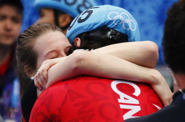 Winner Canada's Charles Hamelin hugs his girlfriend and compatriot speed skater Marianne St-Gelais after the men's 1,500 metres short track speed skating race finals at the Iceberg Skating Palace during the 2014 Sochi Winter Olympics