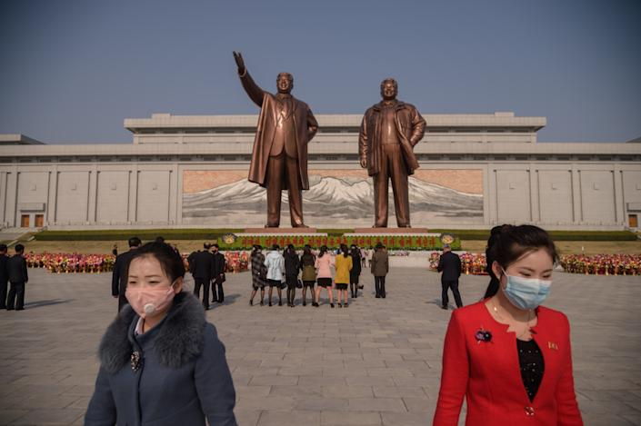 People wearing face masks leave after laying flowers before the statues of late North Korean leaders Kim Il Sung and Kim Jong Il on the occasion of the 108th birthday of late North Korean leader Kim Il Sung in Pyongyang on April 15, 2020. (Photo: Kim Won/AFP via Getty Images)