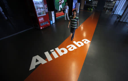 Employee walks pass a logo of Alibaba during a media tour organised by government officials at its headquarters on the outskirts of Hangzhou