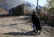 Residents hug as they stand near a house set on fire by departing Ethnic Armenians in the village of Cherektar, in the region of Nagorno-Karabakh