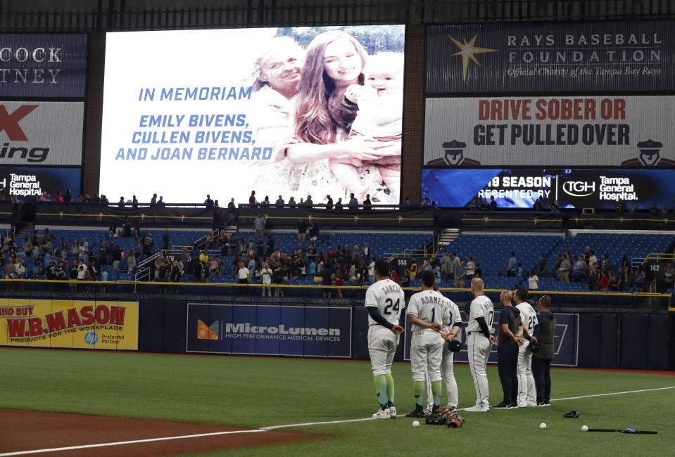 Before a baseball game against the Cleveland Indians, Tampa Bay Rays players stand for a moment of silence in support of Montgomery Biscuit player Blake Bivens whose family was recently murdered, Friday, Aug. 30, 2019, in St. Petersburg, Fla. (AP Photo/Scott Audette)