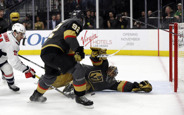 Vegas Golden Knights goalie Marc-Andre Fleury stops a shot from Washington Capitals forward Garnet Hathaway, left, as left wing Tomas Nosek (92) defends during the first period of an NHL hockey game Monday, Feb. 17, 2020, in Las Vegas. (AP Photo/Isaac Brekken)