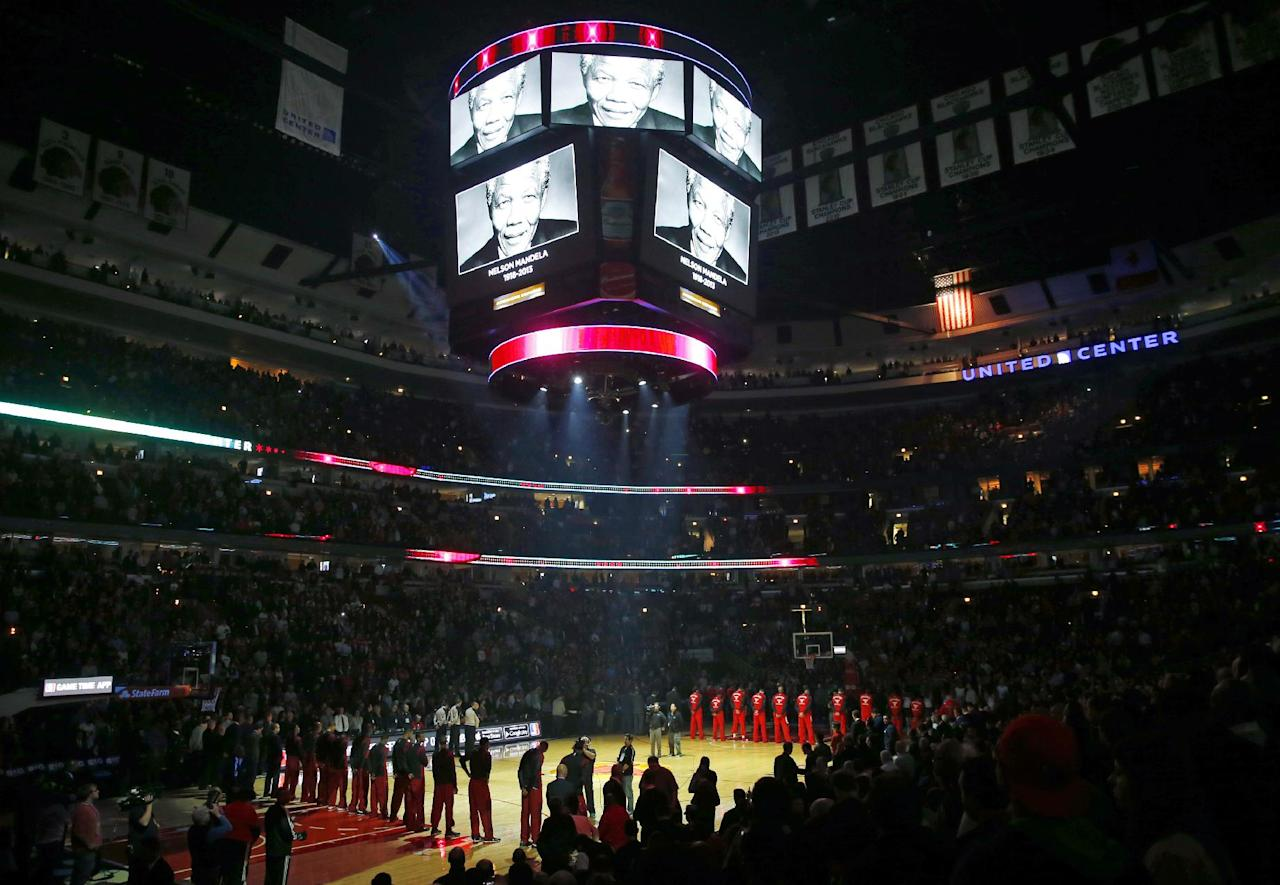 The Chicago Bulls and the Miami Heat players pay the tribute to the Nelson Mandela before their NBA basketball game in Chicago, Thursday, Dec. 5, 2013. Nelson Mandela, the anti-apartheid leader who became South Africa's first democratically elected president and a symbol of reconciliation to many around the world, died Thursday. He was 95. (AP Photo/Kamil Krzaczynski)