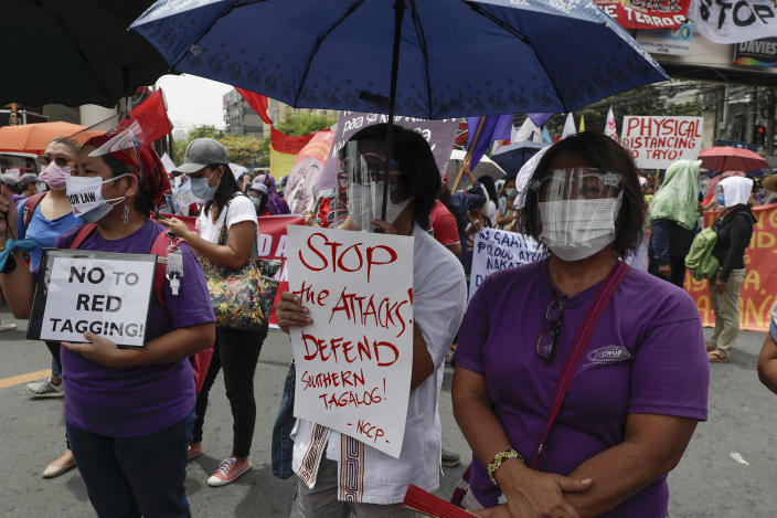Woman activists hold slogans condemning the recent government attacks on activists as they hold a rally near the Malacanang presidential palace to mark International Women's Day on Monday March 8, 2021 in Manila, Philippines. Philippine police backed by military forces killed nine people over the weekend in a series of raids against suspected communist insurgents, with authorities saying the suspects opened fire first. Others, however, said those killed were unarmed activists. (AP Photo/Aaron Favila)