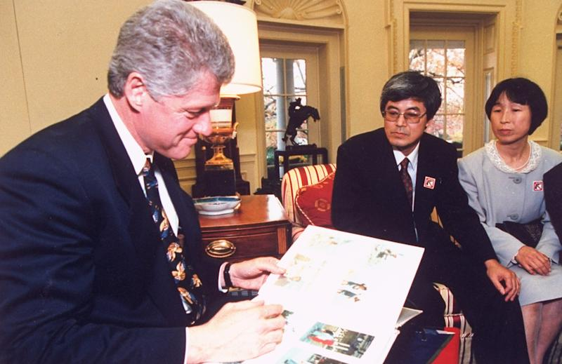 President Bill Clinton looking at photos of Japanese exchange student Yoshihiro Hattori, as parents Masaichi & Mieko. Source: Time Life Pictures/White House/The LIFE Picture Collection via Getty Images.