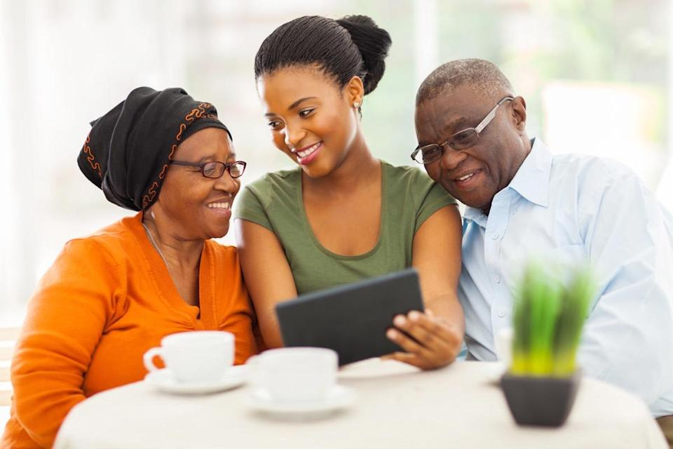 cheerful african family at home using tablet
