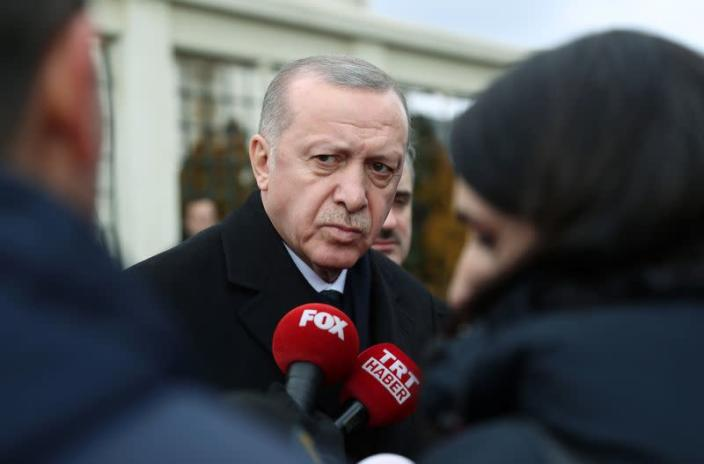 Turkish President Tayyip Erdogan talks to journalists in front of a mosque as he leaves friday prayers in Istanbul