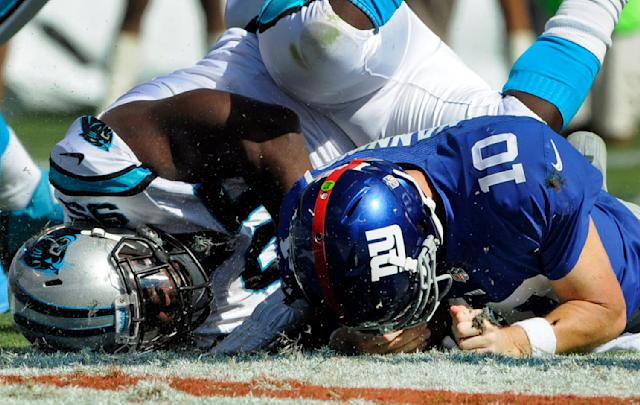 New York Giants' Eli Manning (10) is sacked by Carolina Panthers' Charles Johnson (95) during the second half of an NFL football game in Charlotte, N.C., Sunday, Sept. 22, 2013. The Panthers won 38-0. (AP Photo/Mike McCarn)