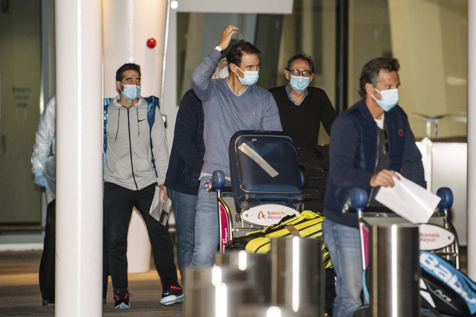 Spain's Rafael Nadal, center, arrives at Adelaide Airport ahead of the Australian Open tennis championship, Adelaide, Australia, Thursday, Jan. 14, 2021. Arriving players will serve a 14-day quarantine period ahead of the first Grand slam tennis tournament that is set to get underway on February 8 in Melbourne. (Morgan Sette/AAP Image via AP)