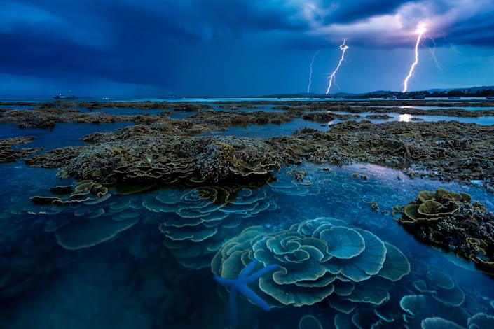 'In the thunderstorm' by @dean_nguyen shows lightning over the coral reefs of  Hon Yen island Vietnam.