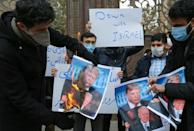 Students burn pictures of US President Donald Trump and President-elect Joe Biden during a demonstration in front Iran's foreign ministry in Tehran on November 28, 2020 following the assassination of a top Iranian nuclear scientist