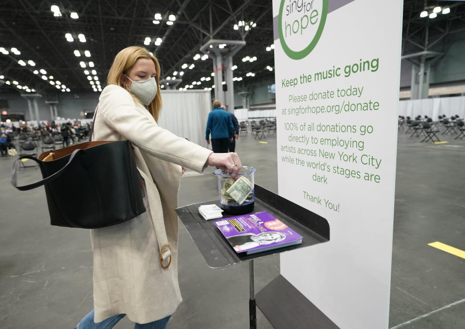 A woman who had just been vaccinated places money into a tip jar for musicians who were playing for health care workers, the public and members of the New York National Guard at the Jacob K. Javits Convention Center, a mass vaccination site, Thursday, March 18, 2021, in New York. Collected by the nonprofit Sing for Hope, the money will to go toward supporting musicians and other performance artists who haven't been able to work since the pandemic darkened New York's stages and cultural spaces last March. (AP Photo/Kathy Willens)
