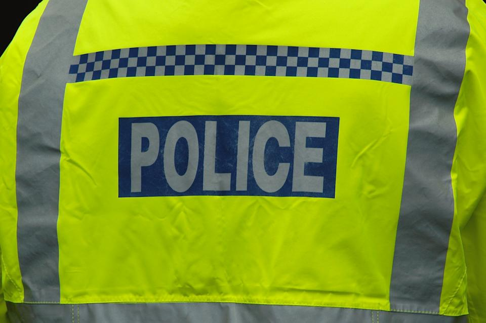 Close-up of a London police officer wearing a high visibility jacket, shot from behind.