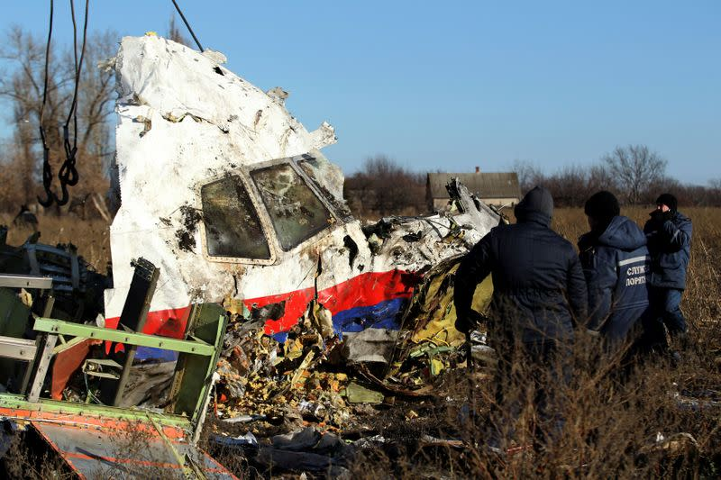 FILE PHOTO: Local workers transport a piece of wreckage from Malaysia Airlines flight MH17 at the site of the plane crash near the village of Hrabove (Grabovo) in Donetsk region