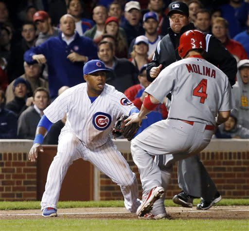 Chicago Cubs third baseman Luis Valbuena takes a throw from relief pitcher Carlos Marmol and catches St. Louis Cardinals' Yadier Molina trying to steal third during the eighth inning of a baseball game, Tuesday, May 7, 2013, in Chicago. (AP Photo/Charles Rex Arbogast)
