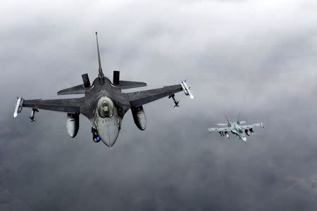 Portuguese Air Force fighter F-16 and Canadian Air Force fighter CF-18 Hornet patrol over Baltics air space, from the Zokniai air base near Siauliai