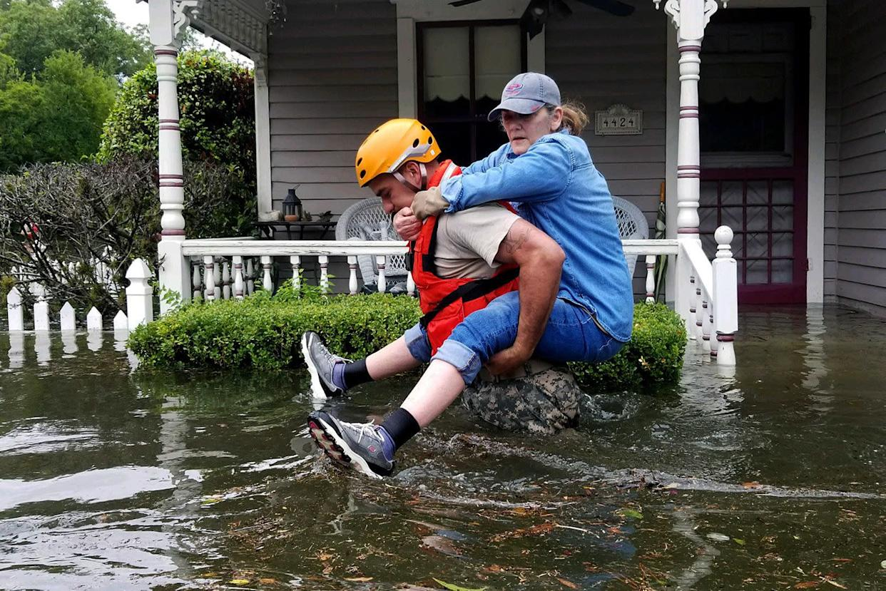 In this handout provided by the Army National Guard, a Texas National Guardsman carries a resident from her flooded home in Houston.