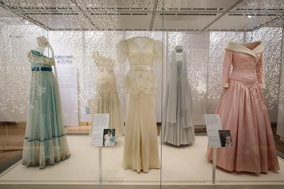A 1990 Bruce Oldfield cream satin dress (C) worn by Princess Diana during a visit to the Courtauld Institute of Art in 1990 and a State Banquet at Buckingham Palace in 1991(C) on display next to a 1987 Catherine Walker pink satin evening gown (R) worn by princess Diana for an official portrait in 1987 as well as during official visits to Germany at the exhibition. (Getty Images)
