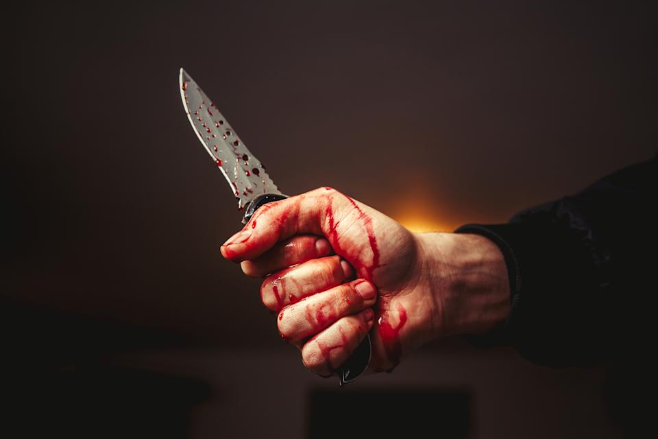 Male hand with bloody knife