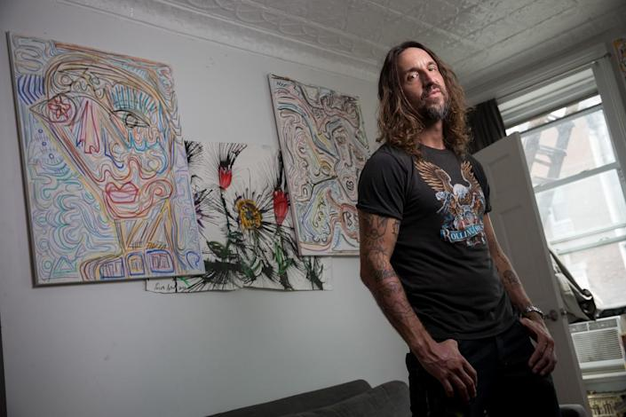 Joseph Arthur stands in front of some of his artworks.