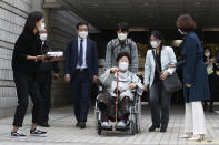 Former South Korean comfort woman Lee Yong-soo in a wheelchair leaves the Seoul Central District Court in Seoul, South Korea, Wednesday, April 21, 2021. The court on Wednesday rejected a claim by South Korean sexual slavery victims and their relatives who sought compensation from the Japanese government over their wartime sufferings. (AP Photo/Ahn Young-joon)