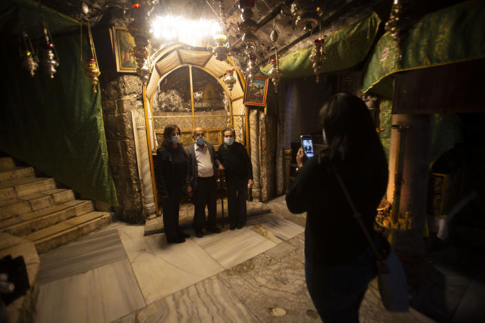 Christian take photos inside the Grotto of the Church of the Nativity, traditionally believed to be the birthplace of Jesus Christ, in the West Bank city of Bethlehem, Monday, Nov. 23, 2020. Normally packed with tourists from around the world at this time of year, Bethlehem resembles a ghost town – with hotels, restaurants and souvenir shops shuttered by the pandemic. (AP Photo/Majdi Mohammed)