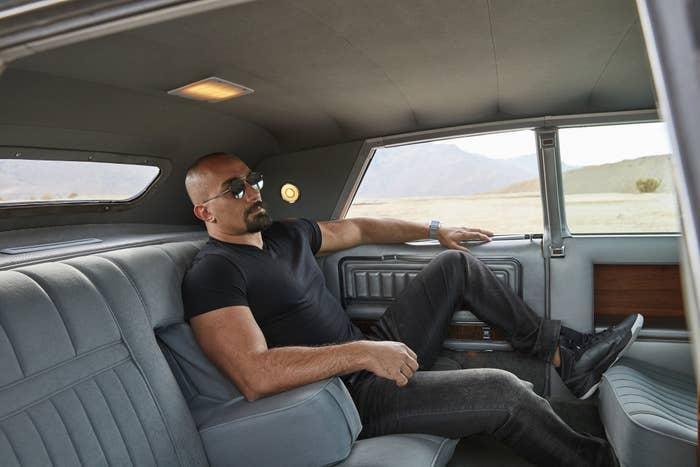 A man lounging in a luxury car