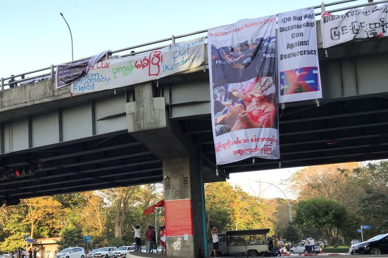 Banner hanging from a bridge shows a woman protester injured by a gunshot wound in the head after police fired to clear the protesters