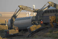 Workers stand on a train car on its side as front-loaders prop up another train car, Sunday, Sept. 26, 2021, from an Amtrak train that derailed Saturday, just west of Joplin, Mont. The westbound Empire Builder was en route to Seattle from Chicago with two locomotives and 10 cars. (AP Photo/Ted S. Warren)