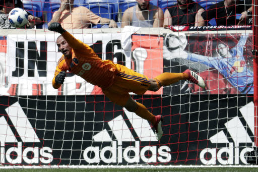 Montreal Impact goalkeeper Evan Bush dives to deflect a shot from the New York Red Bulls during the first half of a soccer match, Saturday, April 14, 2018, in Harrison, N.J. (AP Photo/Julio Cortez)