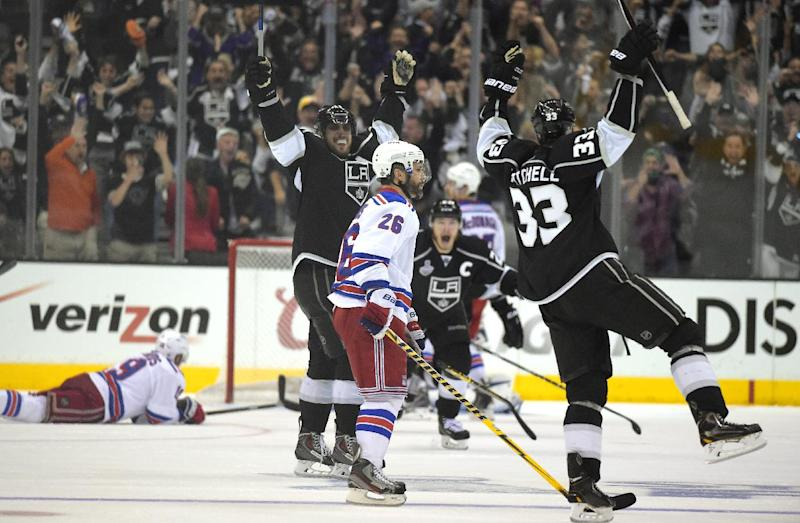 Los Angeles Kings right wing Dustin Brown, center, celebrates after scoring the game-winning goal along with center Anze Kopitar, second from left, of Slovenia, and defenseman Willie Mitchell, right, as New York Rangers center Brad Richards, left, lies on the ice and Martin St. Louis (26) watches during the second overtime period in Game 2 of the NHL hockey Stanley Cup Finals, Saturday, June 7, 2014, in Los Angeles. The Kings won 5-4