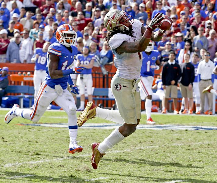 Florida State wide receiver Kelvin Benjamin, right, catches a pass in front Florida defensive back Jaylen Watkins (14) for a 56-yard reception during the second half of an NCAA college football game in Gainesville, Fla., Saturday, Nov. 30, 2013.(AP Photo/John Raoux)
