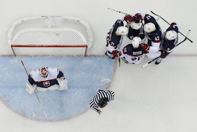 Team USA celebrates Phil Kessel's (81) goal against Slovakia goaltender Jaroslav Halak during the 2014 Winter Olympics men's ice hockey game at Shayba Arena, Thursday, Feb. 13, 2014, in Sochi, Russia. (AP Photo/Matt Slocum)