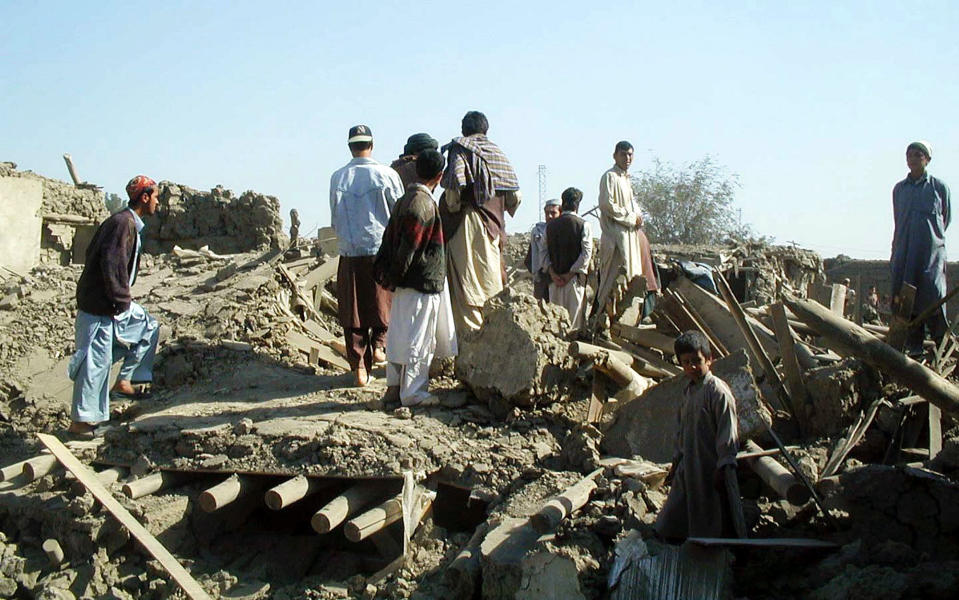 FILE - Residents of Kabul, Afghanistan walk around the rubble of four houses near the airport, Saturday, Oct. 13, 2001, which were destroyed by alliance bombing Friday night. (AP Photo/Amir Shah)