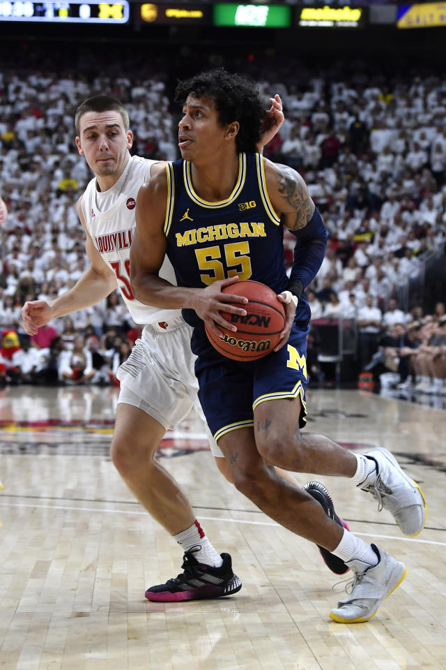 Michigan guard Eli Brooks (55) drives around the defense of Louisville guard Ryan McMahon (30) during the first half of an NCAA college basketball game in Louisville, Ky., Tuesday, Dec. 3, 2019. (AP Photo/Timothy D. Easley)