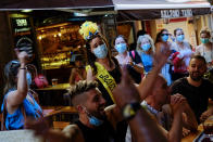 People enjoy a summer's day, in Benidorm, south-east Spain, Saturday, June 26, 2021. Almost a year after face masks became mandatory indoors and outdoors in Spain, people from Saturday are no longer required to wear them outside as long as they can stay at least 1.5 meters (5 feet) apart. (AP Photo/Alvaro Barrientos)