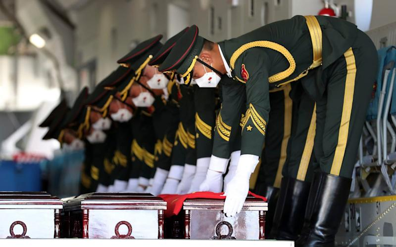 Chinese honor guard members put caskets containing the remains of Chinese soldiers in a cargo airplane during the handing over ceremony - South Korea Defense Ministry