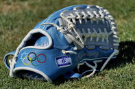The glove of Israel Olympic baseball player Jake Roseberg sits on the field at Salt River Fields spring training facility, Wednesday, May 12, 2021, in Scottsdale, Ariz. Israel has qualified for the six-team baseball tournament at the Tokyo Olympic games which will be its first appearance at the Olympics in any team sport since 1976. (AP Photo/Matt York)