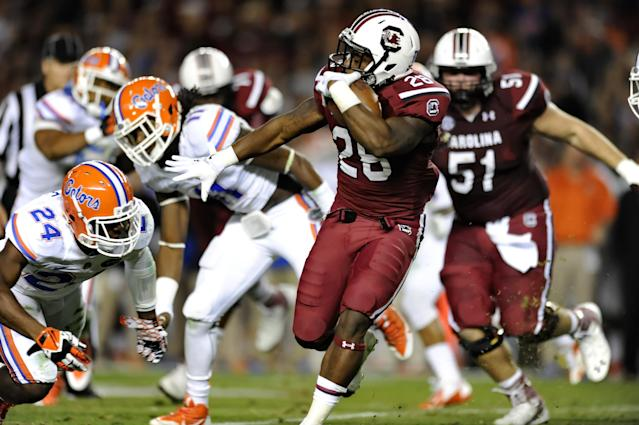 South Carolina running back Mike Davis (28) rushes past Florida's Brian Poole (24) during the first half of an NCAA college football game Saturday, Nov. 16, 2013, at Williams-Brice Stadium in Columbia, S.C. South Carolina won 19-14. (AP Photo/ Richard Shiro)