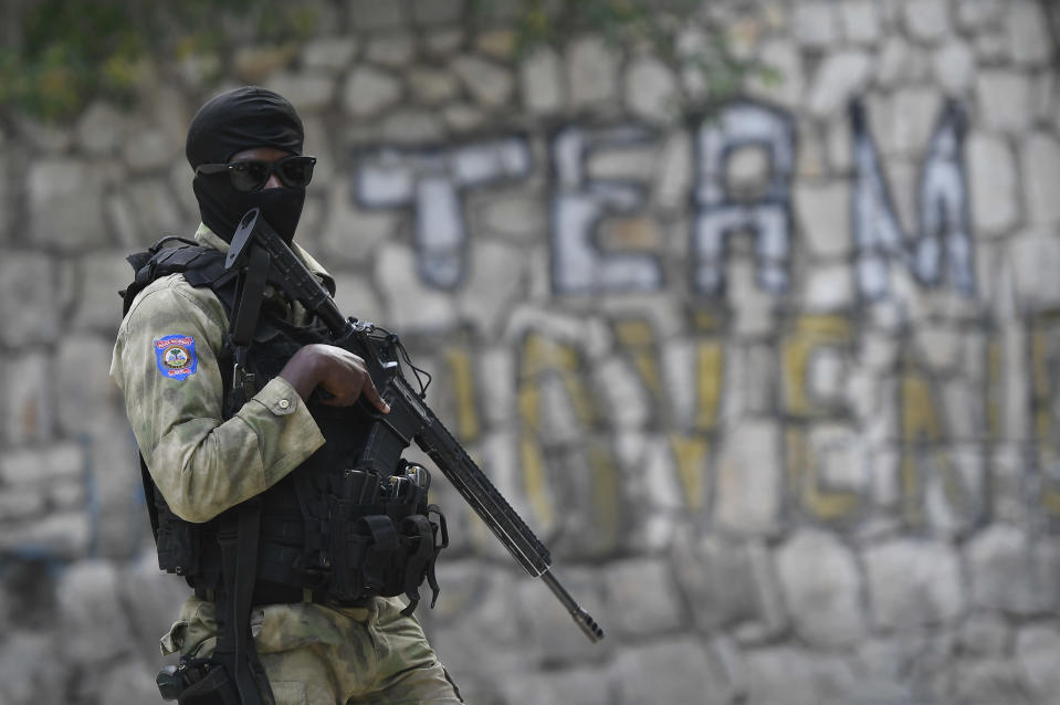A Haitian police officer stands outside President Jovenel Moise´s residence while FBI agents inspect the inside of the place, in Port-au-Prince, Haiti, Thursday, July 15, 2021. President Moise was assassinated in the residence on July 7. (AP Photo/Matias Delacroix)