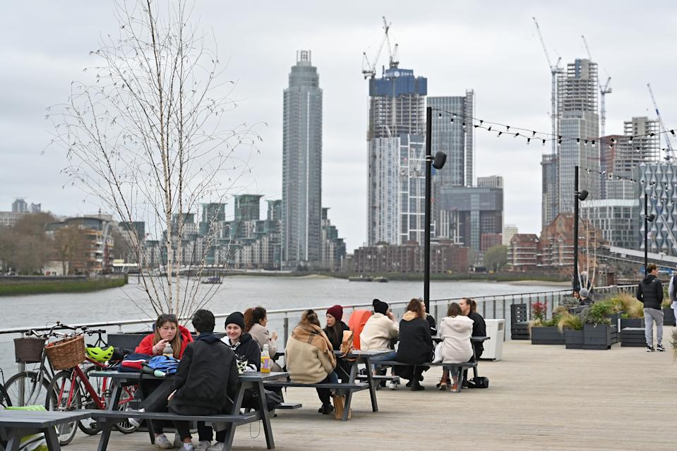 People sit at tables socialising on The Coaling Jetty beside the River Thames in London on March 28, 2021. - From Monday, England's stay-at-home order to combat the spread of the coronavirus will be relaxed to enable groups of up to six people to meet outside. The government plans to allow outdoors drinking in pub gardens, and non-essential retail such as hairdressers, from April 12. (Photo by Justin TALLIS / AFP) (Photo by JUSTIN TALLIS/AFP via Getty Images)