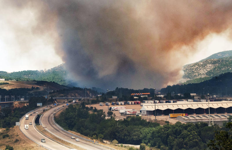 Flames burn the forest near the highway in La Jonquera, Spain, near the border with France, Sunday, July 22, 2012. The regional officials said wildfires have burned almost 7,000 hectares (17.297 acres) of forest. (AP Photo/Josep Ribas)